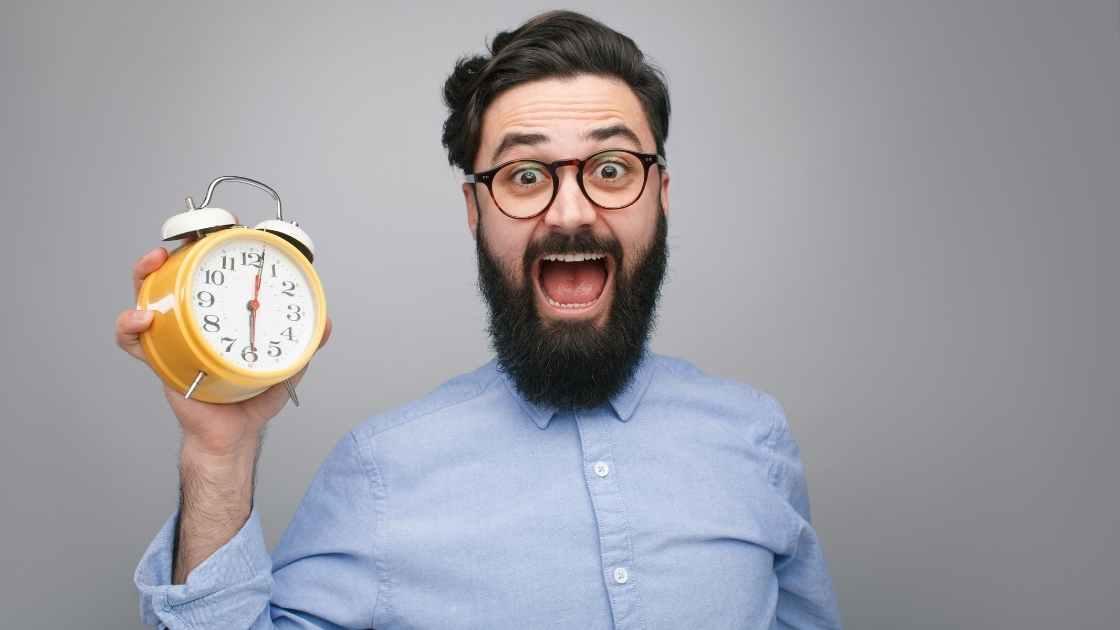 Čovjek s naočalama koji u ruci drži budilicu, a gestama lica odaje dojam da osjeća strah ili zabrinutost