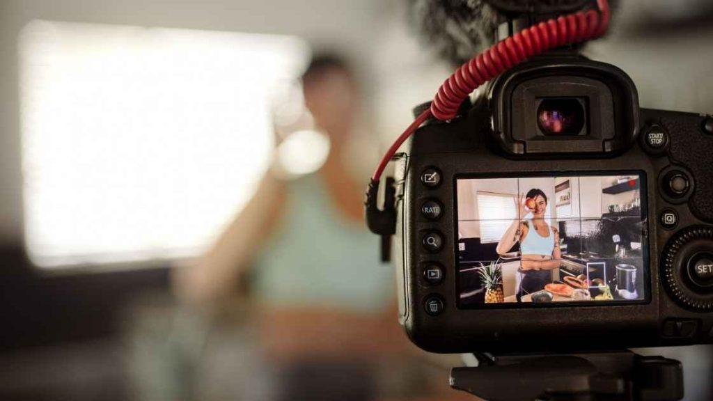 Žena s jabukom u ruci, snima sadržaj za svoj youtube kanal
