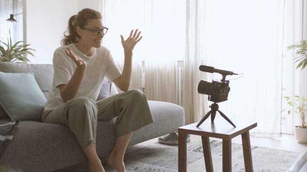 Žena koja s osmijehom na licu, u svome domu na kauču snima sadržaj
