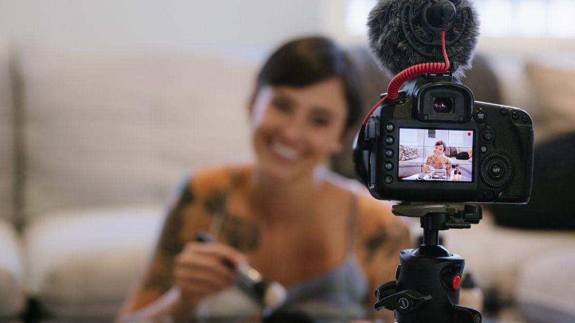 Mlada djevojka sjedi ispred objektiva i snima svoj make up video.