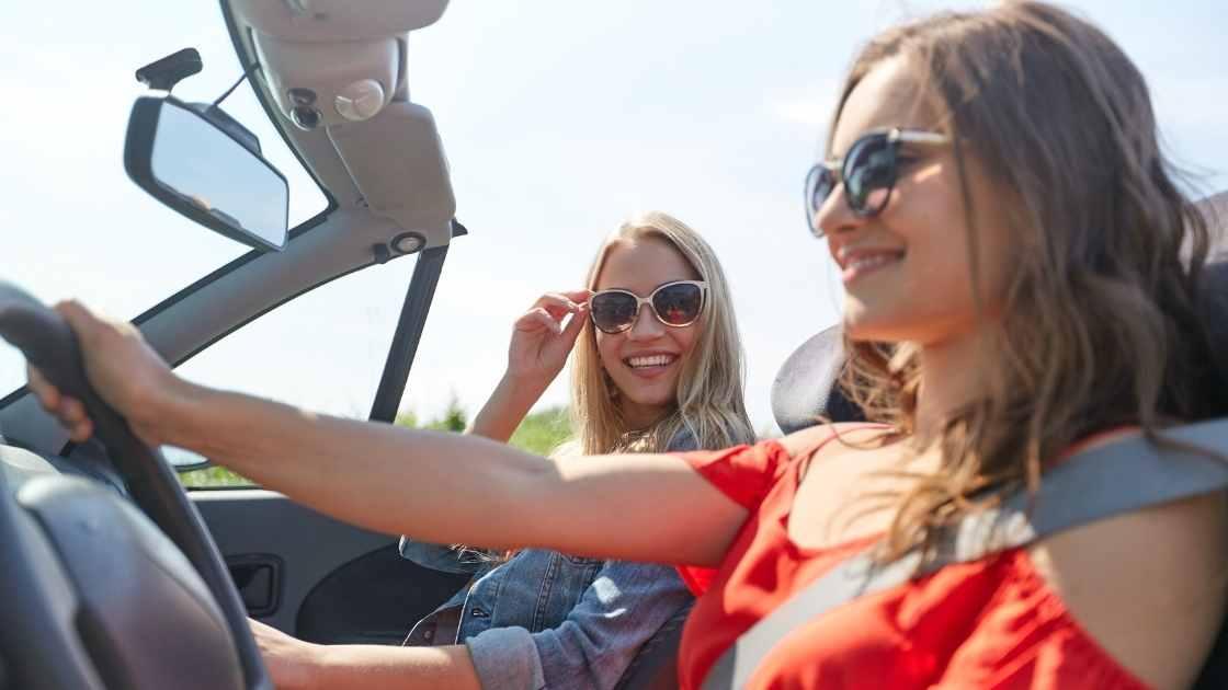 Dvije nasmijane ženske osobe na vozačevom i suvozačevom mjestu u autu